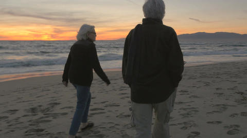 Healthy elderly 60s couple walking and exercising on beach at sunset. Retired fi Footage