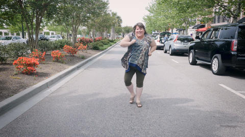 Silly happy smiling woman dancing in street towards camera in urban city environ Footage