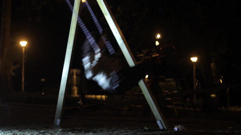 Young girl uses a swing in a park playground, into a warm spring evening 7 Footage