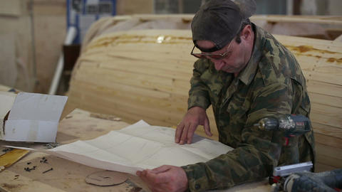 Carpenter studies the draft of the boat at the shipyard Live Action
