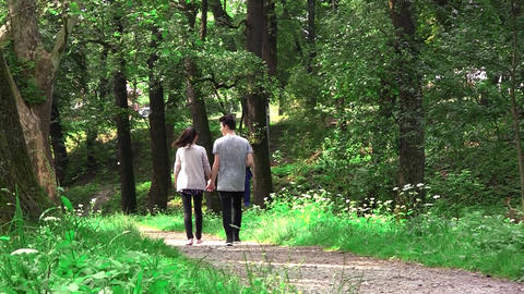 Two young, a girl and a boy walking in an alley in the park. Boy ride a bike, an Footage