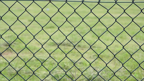 Wire fence, large mesh, sees green grass. In the distance is a large cross as a  Live Action