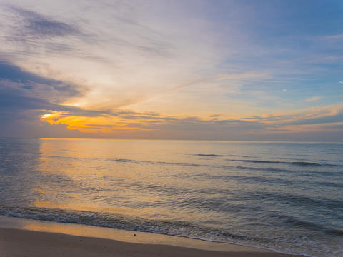 Sunrise and sea waves on beach at sea in the morning フォト