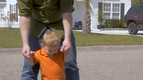 A father helps his cute adorable baby boy take his first steps while holding his Footage
