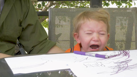 A tired cranky young toddler boy crying while sitting at a table coloring with h Footage