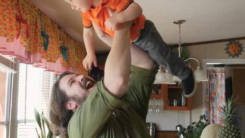 Stay at home dad lifting and playing with his happy smiling baby boy in the air  Footage