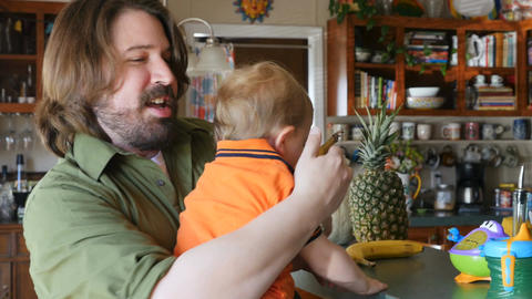 A handsome dad in his 30s peels a ripe banana and gives his toddler son a piece. Footage
