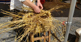 A 4k video of a man platting the top of a straw hand made basket Archivo