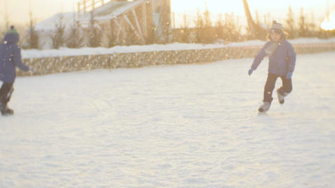 Boys Skate on Rink Give Five Each Other against Setting Sun Footage