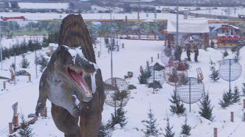 Flycam Rotates around Large Dinosaur Sculpture against Park Footage