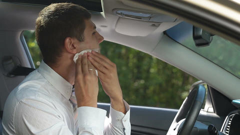 Businessman cleaning lipstick from cheek in car Image