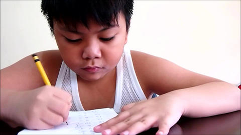 A young boy answering a school worksheet Footage