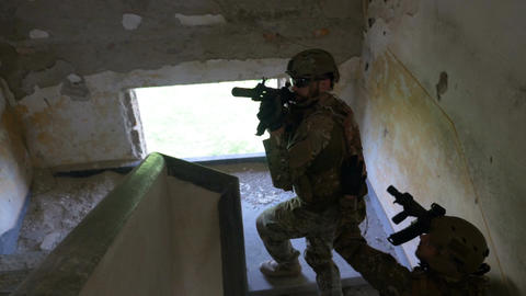 Young soldiers on a mission to kill terrorists ascending on stairs to first floo Footage