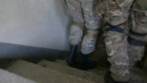 Closeup of soldier feet walking through abandoned building stairs in team exerci Footage