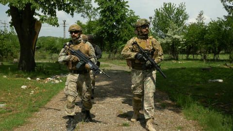 Military unit walking and patrolling near abandoned building on a sunny day look Footage
