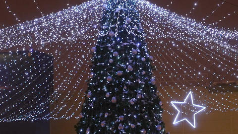 Motion up along Christmas Tree Decorated with Balls and Garlands Footage