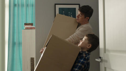Father Son Carry on Heavy Boxes from Door to Room in Apartment Footage