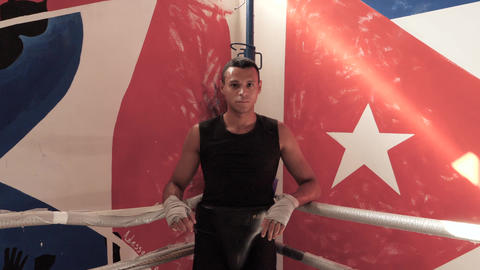 Sweaty male boxer leaning on ropes looking at camera Footage