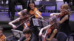 Girls musicians play violins in the orchestra Footage