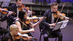Violinists orchestra musicians are playing music on violins on stage Footage