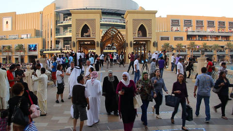 Many people at evening, bridge to Dubai Mall, modern downtown area Live Action