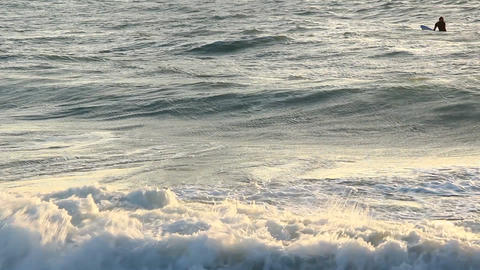 Close water surf at sunset time, wave crest break to white foam, telephoto Footage