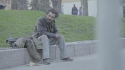 A crisis. The homeless beggar sits on the street Footage