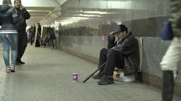 Poverty. Beggar in the underground subway passage. Homeless Footage