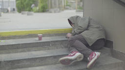 A tramp asleep on the street on the steps Footage