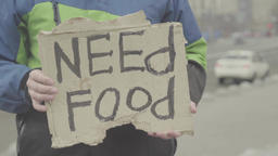 "The inscription ""Need food"" on a cardboard in the hands of a beggar Footage"