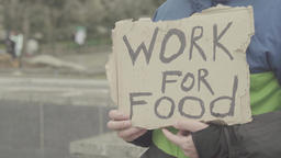 "The inscription ""Work for food"" on a cardboard in the hands of a beggar Footage"