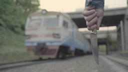 Man killer maniac goes with a knife in his hand by rail past the train Footage