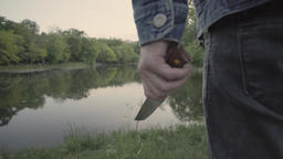 Murderer-a maniac with a knife near a lake in the park Footage