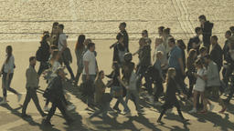 Many people cross the road on a pedestrian crossing. Crowd Footage