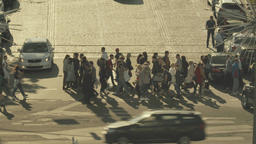 Cityscape. A crowd of people cross the road on a pedestrian crossing Footage