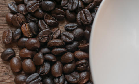 Coffee beans on wooden desk background Photo