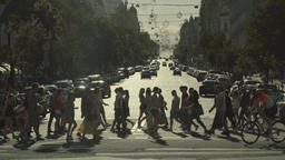 A crowd of people cross the road on a pedestrian crossing. Slow Motion Footage