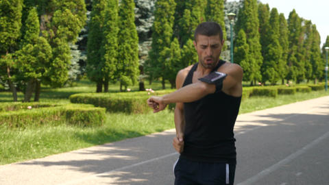 Athletic man jogging in the park and checking smart phone fitness tracker app Footage