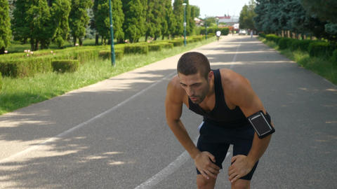 Handsome athletic man training on running track using wearable tracker gadget Live Action
