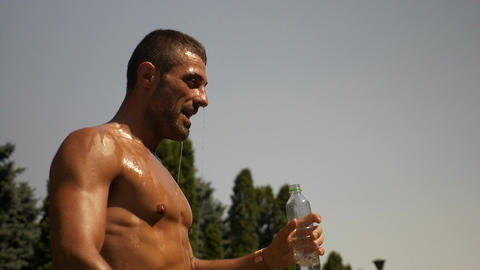 Wet body builder with water over his body in hot summer day Footage