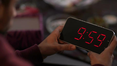 Cinemagraph of man holding a digital clock and looking at the time passes and go Image