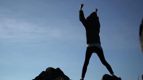 Woman raising arms victoriously after climbing the mountain Footage