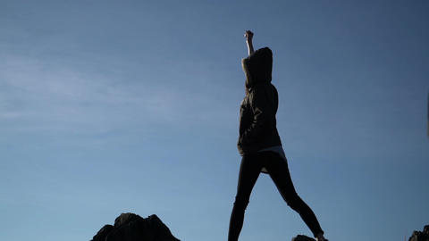 Woman raising arms victoriously after climbing the mountain Filmmaterial