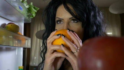 Happy vegan woman opening fridge smelling fruits and taking an apple for brunch Footage