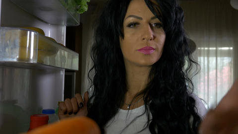 Fit woman on diet opening refrigerator and tasting a fresh carrot Live Action