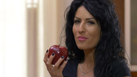 Attractive female relaxing at home while eating a red delicious apple enjoying h Footage