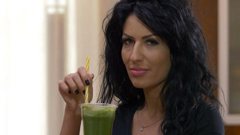 Happy woman on a low caloric diet enjoying a delicious vegetable smoothie Live Action