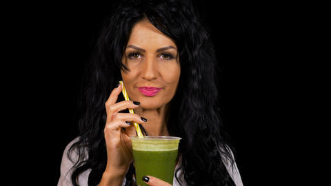 Attractive woman healthy drinking and enjoying a green smoothie Live Action