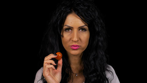 Joyful woman on a vegan diet eating cherry tomatoes concept of healthy nutrition Footage
