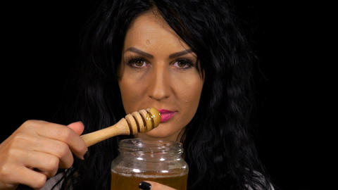 Smiling healthy woman eating honey from a jar Live Action